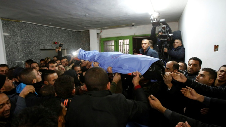 Relatives carry a Palestinian man killed while allegedly carrying out attacks on Israelis, after Israeli authorities returned his body to the Al-Ahli hospital on December 16, 2016, in the West Bank city of Hebron