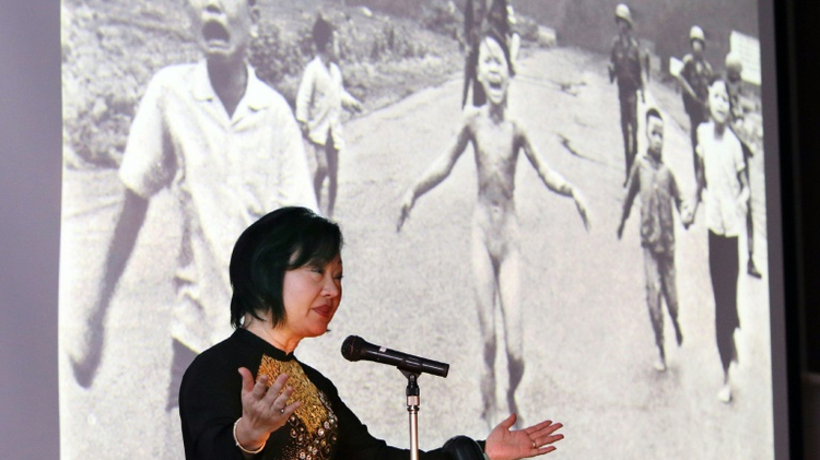 Kim Phuc stands beside the 1972 Pulitzer winning photograph of her running naked and burnt by napalm during the Vietnam War, as she addresses delegates during a 2013 conference in Nagoya, Japan