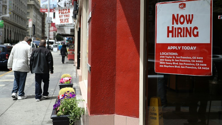 A 'now hiring' sign is posted in the window of a fast food restaurant on July 8, 2016 in San Francisco, California