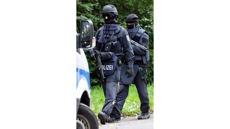 "Four German police officers were wounded, some of them seriously, when a member of the far-right ""Citizens of the Reich"" group opened fire during a raid October 19, 2016"