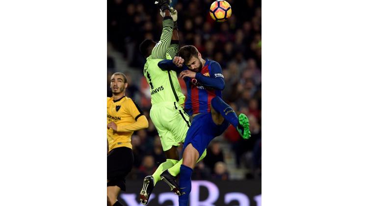 Barcelona's Gerard Pique (R) vies with Malaga's goalkeeper Carlos Kameni on November 19, 2016