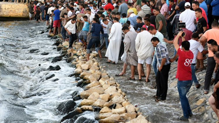 مصريون يتابعون عملية انتشال جثث ضحايا قارب المهاجرين الذي غرق قبالة ساحل مدينة رشيد في شمال مصر