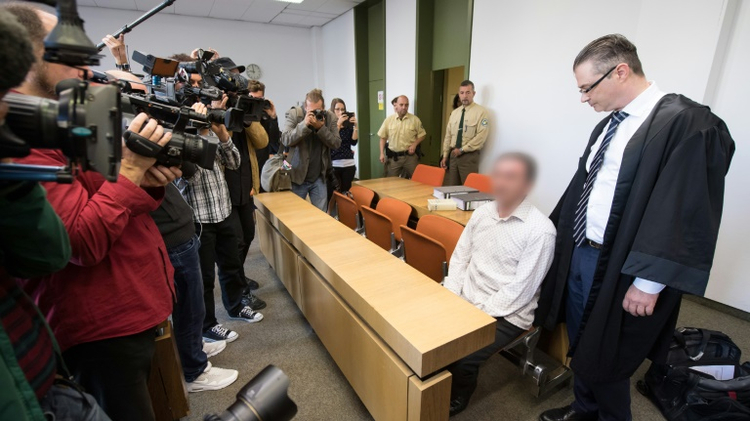 Vucelic V., accused of helping to prepare a terror attack after police found Kalashnikovs and explosives hidden in his car while he was driving to Paris last November, arrives at the courtroom of the Munich District Court on September 23, 2016
