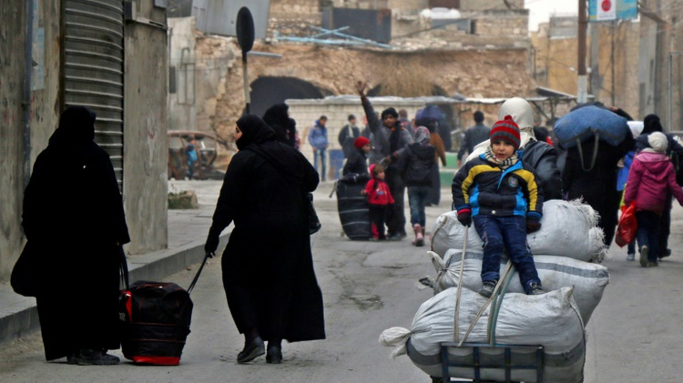 Residents of eastern rebel-held parts of Aleppo, northern Syria walk through the Kadi Askar district on November 30, 2016 as they leave their homes for a safer place, during a Syrian army offensive on the eastern sectors of the divided city