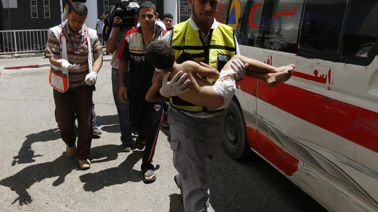 An emergency worker carries a child wounded in an Israeli air strike on the Sheikh Radwan area of Gaza City, as he arrives at the city's Al-Shifa hospital, on August 8, 2014
