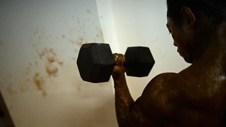 A bodybuilder lifts weights backstage as he warms up ahead of the final SEA Games selection contest in Yangon on February 12, 2013