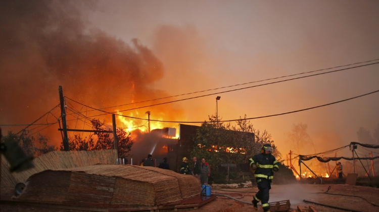 Firefighters helps extinguish a new fire that broke out in the Israeli town of Nataf, west of the Arab Israeli town of Abu Ghosh, along the border with the occupied West Bank on November 25, 2016