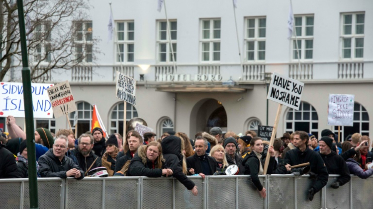 """Demonstrators hold posters reading """"Have you no shame"""" during a protest outside the parliament in Reykjavik on April 6, 2016 following the Panama Papers revelations"""