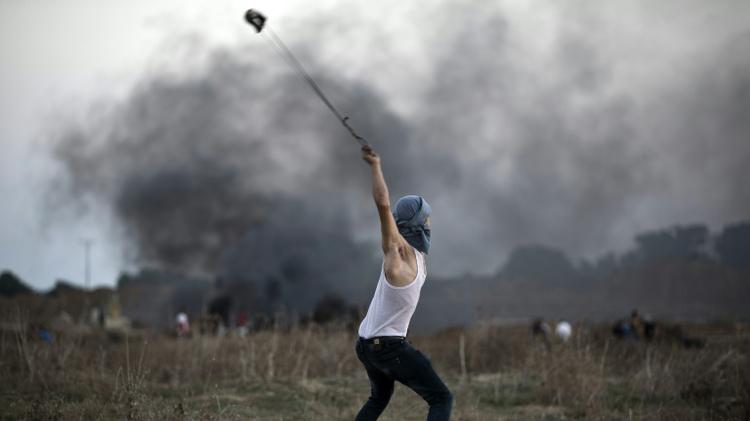 Un Palestinien lance une pierre en direction de l'armée israélienne dans la ville de la bande de Gaza de Bureij, le 15 octobre 2015
