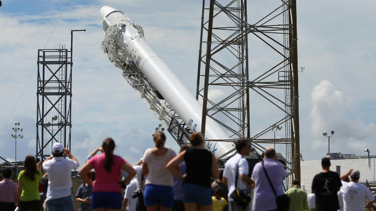 A SpaceX Falcon 9 rocket is raised into launch position at Cape Canaveral, Florida, in October 2012