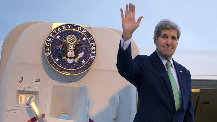 US Secretary of State John Kerry waves as he boards his plane at Paris' Orly Airport en route to Vienna, on October 15, 2014
