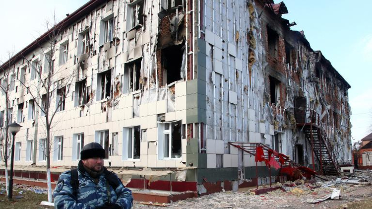 A serviceman guards a school building damaged during fighting between militants and police, in Grozny, Chechnya, on December 5, 2014