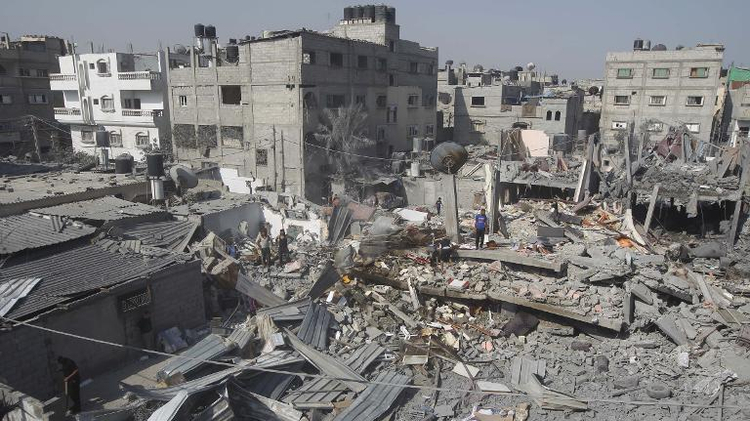 Palestinians inspect the wreckage of a building which was hit in an Israeli strike on the southern gaza town of Rafah, on August 2, 2014