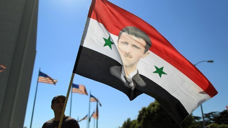A Syrian supporter of President Bashar al-Assad waves a flag during a rally in Los Angeles, on September 7, 2013