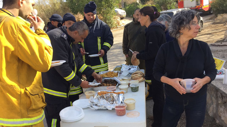 Palestinian and Israelis take a break together after night of fighting fires in Nataf