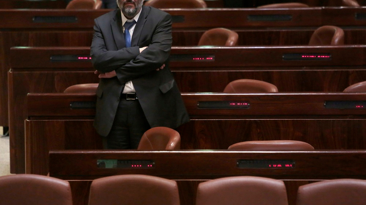 Israeli religious Shas party leader Aryeh Deri standing in the Knesset (Parliament) plenum in Jerusalem on 08 December 2014.