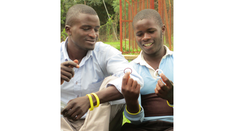 Young men in Rwanda holding the PrePex device