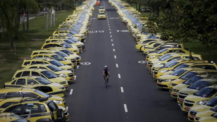 A man rides his bicycle between taxis parked on the street during a protest against the online car-sharing service Uber in Rio de Janeiro, Brazil July 24, 2015
