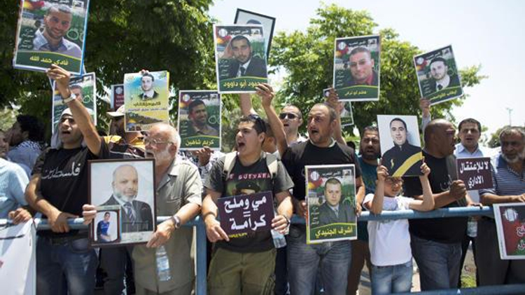 Palestinian activists hold placards during a protest outside the Israeli run Ayalon prison in Ramle, near Tel Aviv, calling for the release of Palestinian prisoners, on May 23, 2014, as they express solidarity with Palestinian prisoners who are on hunger