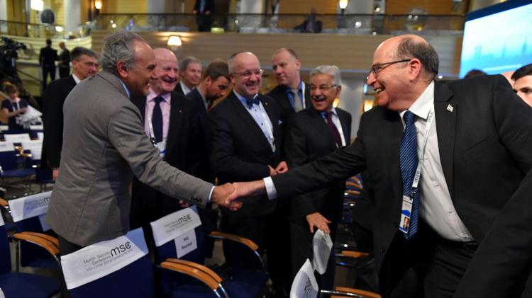 Israeli Defense Minister Ya'alon shakes hands with Saudi Prince Turki al-Faisal