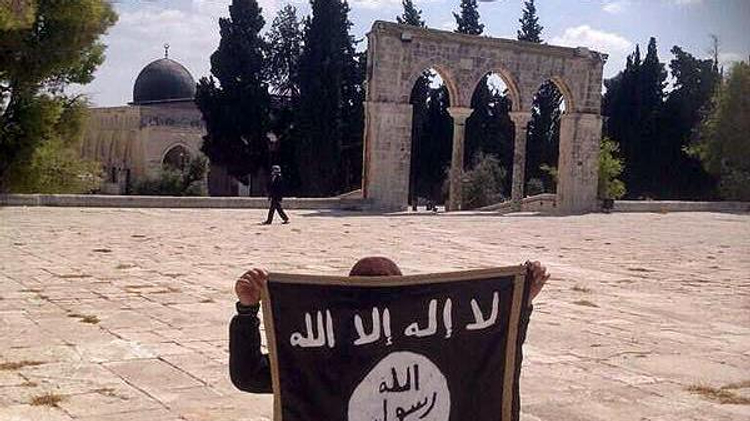 A boy holding up the Islamic State flag on the Temple Mount in Jerusalem in 2014