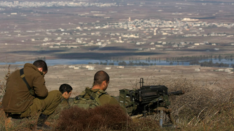 Israeli soldiers in an abandoned military outpost overlooking the ceasefire line between Israel and Syria on Tal Hazika near Alonei Habshan in the Golan Heights on November 15, 2012