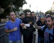 People detain after disarming an Orthodox Jewish assailant, after he stabbed and injured six participants of an annual gay pride parade in Jerusalem on Thursday, police and witnesses said July 30, 2015. ( REUTERS/Amir Cohen )