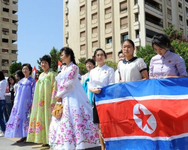 Young women hold a North-Korean flag during a ceremony to name a park in Damascus after Kim Il-sung, the late founder and supreme leader of the Democratic People's Republic of Korea (DPRK), on Aug 31, 2015 in the Kafar Susseh neighbourhood. ( AFP )