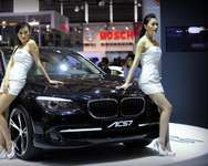Scantily clad female models pose on a customized BMW at the Auto Shanghai, in 2009 ( Peter Parks (AFP/File) )