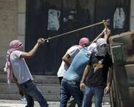 Palestinian protesters fire stones toward Israeli police using a slingshot during clashes in the Shuafat neighborhood in Israeli-annexed Arab east Jerusalem, on July 2, 2014, after a Palestinian teenager was kidnapped and killed ( Ahmad Gharabli (AFP) )