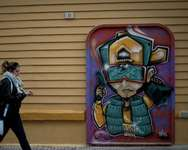 Street art is pictured on a building as a pedestrian passes in Malaga on January 12, 2015 ( Jorge Guerrero (AFP) )