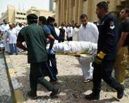 Kuwaiti security personnel and medical staff carry a man on a stretcher at the site of a suicide bombing that targeted the Shiite Al-Imam al-Sadeq mosque on June 26, 2015, in Kuwait City ( AFP )