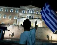 A man holds a Greek national flag as he celebrates in front of the parliament on July 5, 2015 in Athens ( Iakovos Hatzistavrou (AFP) )