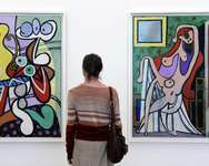 A visitor looks at Picasso paintings 'Large nude in a red armchair 1929' (R) and 'Large still life  with a pedestal table 1931', at the Picasso museum in Paris, on October 18, 2014 ( Bertrand Guay (AFP/File) )