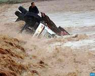 Drivers cling to their overturned truck in flood waters in Morocco's southern region of Ouarzazate ( AFP )