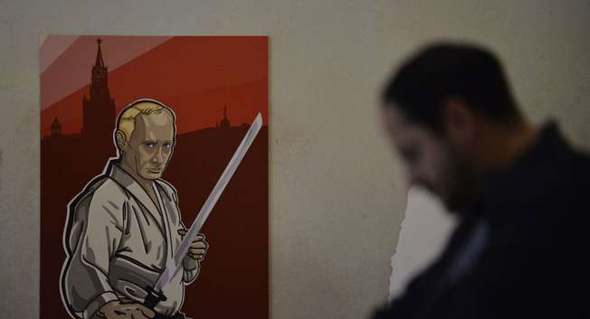 "A visitor passes by an artwork depicting Russian President Vladimir Putin as Japanese author Yukio Mishima during the ""Putin Universe"" exhibition in Moscow on October 6, 2015 ( AFP/ NATALIA KOLESNIKOVA )"