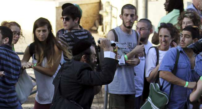 An Orthodox Jewish assailant (C) stabs participants at an annual gay pride parade, wounding six, in Jerusalem on Thursday, police and witnesses said July 30, 2015. ( REUTERS/Amir Cohen )