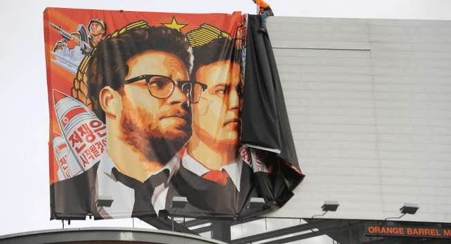 "Workers remove a poster-banner for ""The Interview"" from a billboard in Hollywood, California, December 18, 2014 ( Michael Thurston (AFP/File) )"