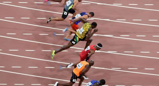 """Jamaica's Usain Bolt (C) competes in the heats of the men's 100 metres athletics event at the 2015 IAAF World Championships at the """"Bird's Nest"""" National Stadium in Beijing on August 22, 2015 ( Johannes Eisele (AFP) )"""