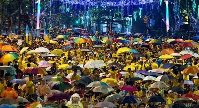 Protestors take shelter under umbrellas during a rain-shower on the second day of the anti-government rally in Kuala Lumpur on August 30, 2015 ( Manan Vatsyayana (AFP) )