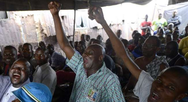 People react in the Obalende district of Lagos on March 31, 2015 as partial results of the Nigerian presidential elections are released by the Independent National Electoral Commission indicating the opposition APC presidential candidate is ahead ( Pius Utomi Ekpei (AFP) )