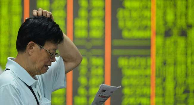 An investor reads a newspaper before a screen showing share prices at a securities firm in Hangzhou, in eastern China's Zhejiang province on August 24, 2015 ( AFP )