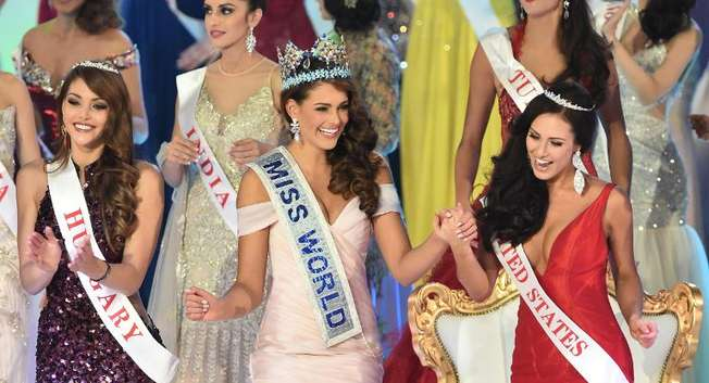 Miss South Africa and the 2014 Miss World, Rolene Strauss (C), dances with first runner up Miss Hungary Edina Kulcsar (L) and second runner up Miss United States Elizabeth Safrit (R) during the grand final in London on December 14, 2014 ( Leon Neal (AFP) )