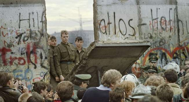 A photo taken early November 11, 1989 of West Berliners watching East German border guards demolishing a section of the Berlin Wall to open a new crossing point between East and West Berlin ( Gerard Malie (AFP/File) )