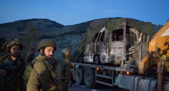 اسرائيليون ينقلون مركبة محترقة من مكان استهداف حزب الله لموكب عسكري اسرائيلي في قرية الغجر ( مناحم كاهانا (اف ب) )