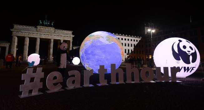 A WWF activist dressed as a panda bear stands next to an illuminated globe in front of the Brandenburger Gate in Berlin during the the global climate change awareness campaign Earth Hour on March 28, 2015 ( John MacDougall (AFP) )