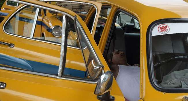 An Indian taxi driver rests in his parked car in Kolkata on May 25, 2015 ( Dibyangshu Sarkar (AFP) )