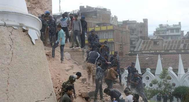 Nepalese rescue members gather at the collapsed Darahara Tower in Kathmandu, on April 25, 2015 ( Prakash Mathema (AFP) )