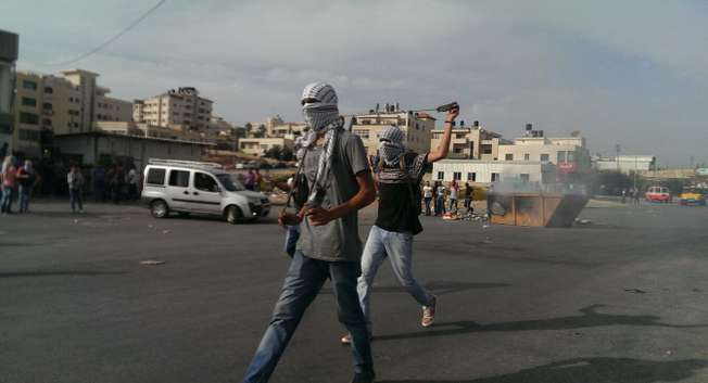 Two Palestinians with sling shots walk along a street in Ramallah, the West Bank ( Naseeb Safadi/ i24news )