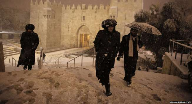 Ultra-Orthodox Jewish men walk near Damascus Gate in Jerusalem's Old City as snow falls ( Ahmad Gharabli/AFP )